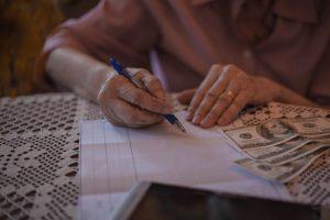 Old woman calculating bills at home.
