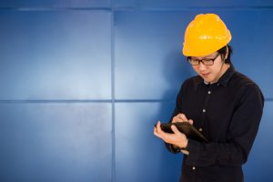 Young Asian engineer man wearing personal yellow protective safety helmet writing on digital tablet. Working on engineering site concept