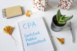 CPA Certified Public Accountant written in notebook on white table
